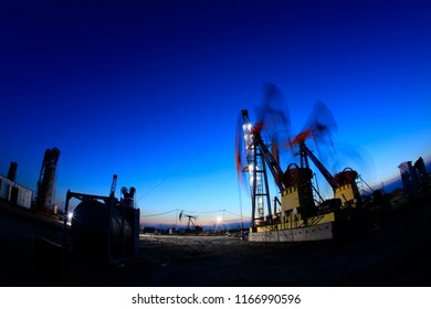 Oil field, oil drilling rig in the evening