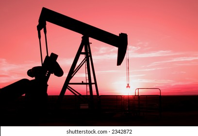 Oil field pump jack with setting sun in background