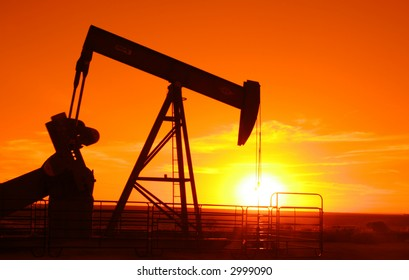 Oil field pump jack with a setting sun in background