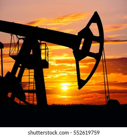Oil Field. Oil pump on  background of  colorful sunset.