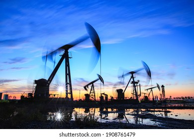 Oil field site, in the evening, oil pumps are running, The oil pump and the beautiful sunset reflected in the water, the silhouette of the beam pumping unit in the evening.