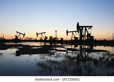 Oil field site, in the evening, oil pumps are running, Silhouette of beam pumping unit