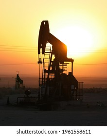 Oil field site with pumps working in California, pump jack at oil well silhouetted against bright morning sun, oil industry graphic for poster, news, background, wallpaper.
