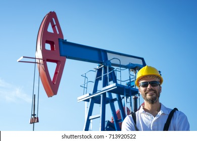 Oil field worker standing in front of the oil pump. Oil rig and industry concept.