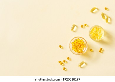 Oil filled capsules (softgel) of food supplements: fish oil, omega 3, omega 6, omega 9, vitamin A, vitamin D3, vitamin E, evening primrose oil, borage oil. Yellow softgels, top view, copy space.