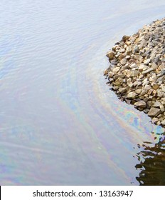 oil film pollution on top of water damage to environment sea stone bank