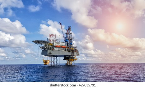 Oil and gas drilling rig working on remote wellhead platform to drill the oilfield reservoir industry