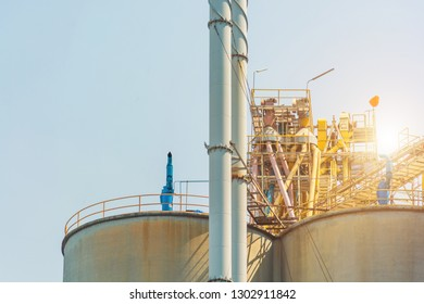 Oil and gas industrial,Oil refinery plant form industry,Refinery factory oil storage tank and pipeline steel with sunset and cloudy sky background,