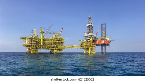 Oil and gas industries. Panorama of red jacket rig drilling on top of well head platform in the middle of the sea. New oil and gas central processing platform installation at North Malay Basin.
