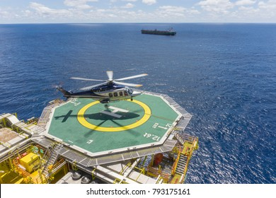 Oil and gas industry. A commercial helicopter landing on helideck at oil and gas platform in with backgroud open sea and tanker.