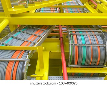 Oil and gas industry. High voltage electrical cables layout on cable tray and yellow steel structure at oil and gas platform.