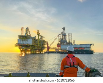 Oil and gas industry. Marine crew standing on supply vessel looking oil and gas platform during sunrise.