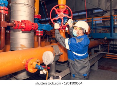 Oil, gas industry. New technology for equipment quality control: The mechanic - the repairman diagnoses equipment using new technologies. Work in production in a mask, during the Covid-19 pandemic.