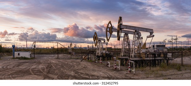 Oil and gas industry. Panoramic of a pump jack and oil refinery.