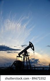 Oil and gas industry. Silhouette oil pump on a sunset sky background.