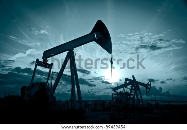 Oil and gas industry. Silhouette oil pumps on a sunset sky background. Toned.