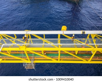 Oil and gas industry. View of oil and gas pipeline on the bridge structure in the middle of the sea while a group of abseiler with Personal Protective Equipment (PPE) working at height and overboard.