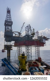 oil and gas industry. View of oil and gas tripod jack up rig holding well head platform and support vessel in the middle of the sea.