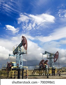 Oil and gas industry. Work of oil pump jack on a oil field. White clouds and blue sky