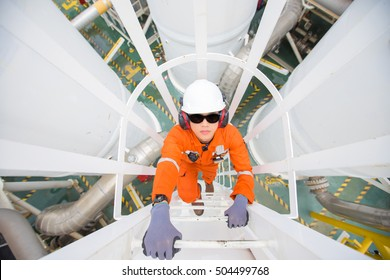 Oil and gas industry worker climb up to pressurized gas vessel for checking  oil and gas dehydration process at the top of vessel, oil rig worker.