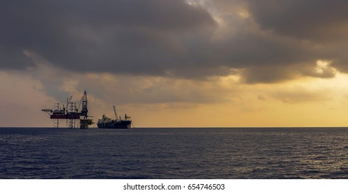 Oil and Gas Production Platform Silhouette view with cloudy golden sky background