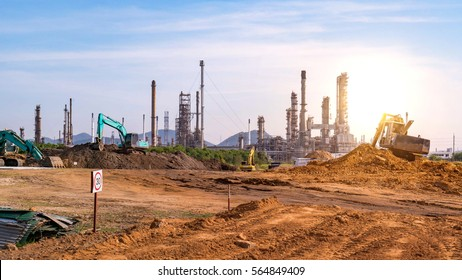 Oil and gas refinery construction site and tractors, petrochemical plant area at Sunset with blue sky