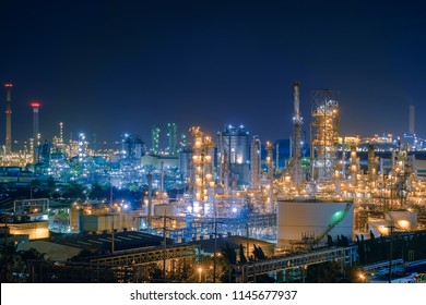 Oil and Gas refinery industry plant with glitter lighting, Factory of petroleum industrial at night time, Petrochemical plant with gas distillation tower and storage tank