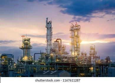 Erdöl- und Erdgasraffinerien oder petrochemische Industrie auf sonnenunterem Hintergrund, Fabrik am Abend, Herstellung von Erdölindustrieanlagen