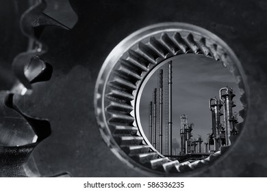 oil and gas refinery seen through a giant gears and cogwheel, industrial concept in black and white