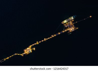 oil and gas terminal on the sea with shipping loading oil business industry import and export open sea aerial top view at night time