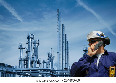 oil and gas worker with large refinery industry in background