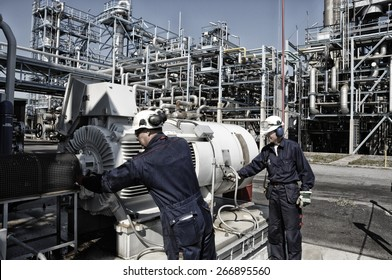 oil and gas workers with machinery inside large refinery
