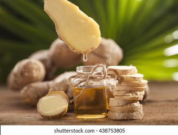 Oil of ginger in a small glass bottle macro and root on tropical leaves background