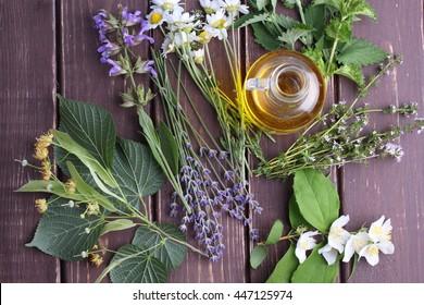 oil with herbs on dark wooden background