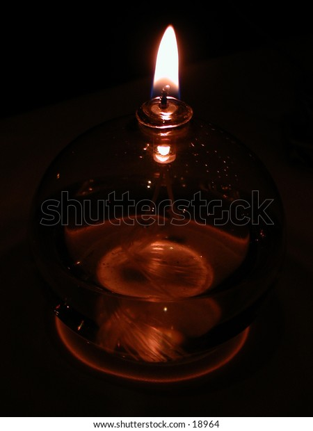 Oil lamp with a flame in an upright position.