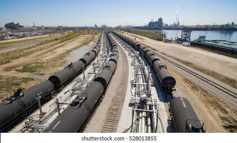 Oil loading facility with tank cars along railroad track and river.