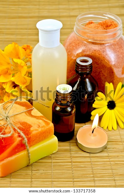 Oil and lotion bottles, two homemade soap, orange bath salt, nasturtium and marigold flowers, a candle on a bamboo mat