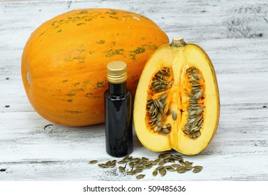 Oil made from pumpkin seeds, oil pumpkin cut in half, fresh pumpkin seeds around