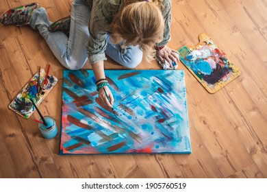 Oil painting. Artist sitting on floor and working on her abstract paintings. Female art painter in her studio