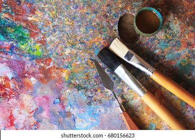 Oil paints palette with paint brushes and palette knife - Shutterstock ID 680156623