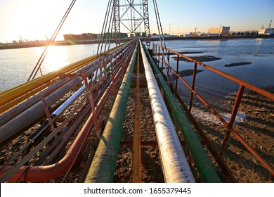 The oil pipeline on the bridge, silhouetted in the sunset