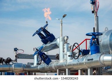 Oil pipes and valves and gas flame in refinery