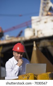 An oil platform inspector with his laptop, with the platform in the background
