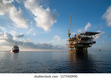 oil platform at sea with offshore vessel nearby during morning