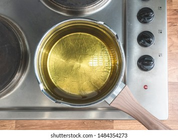 Oil in a pot situated over the stove. View from above