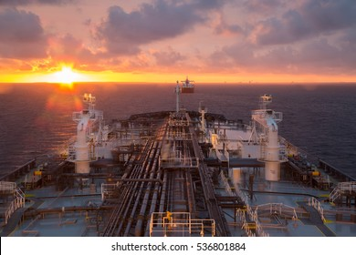 Oil product tanker during beautiful sunset at anchor.