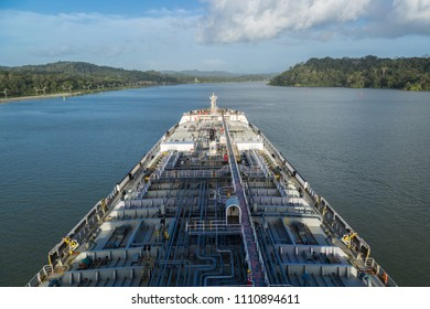 Oil product tanker proceeding through Panama Canal by jungle.