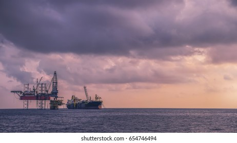 Oil Production Platform with drilling rig and FPSO facility ship in offshore field