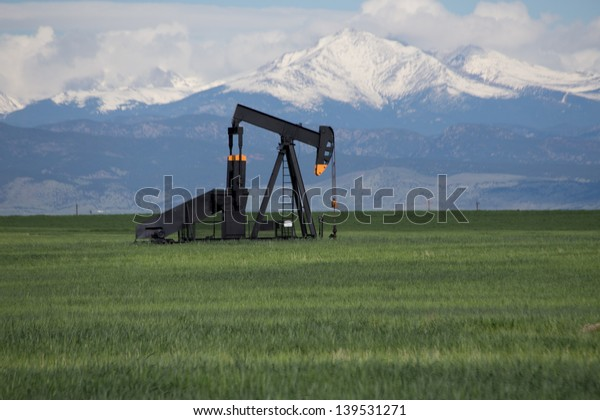 Oil Pump in Green Field With Snow Covered Rocky Mountains and Blue Sky