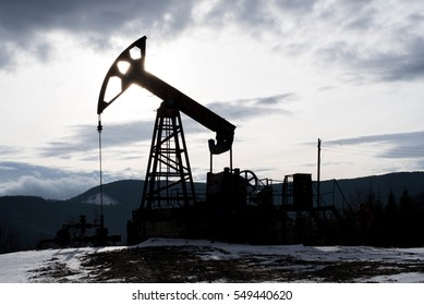 The oil pump, industrial equipment. Oil rig sunset. Oil pumps on the sunset sky in winter mountains background. Oil industry equipment.